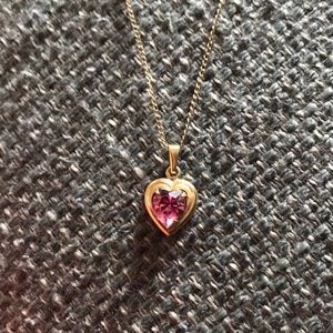 Gold heart necklace with pink gem in center
